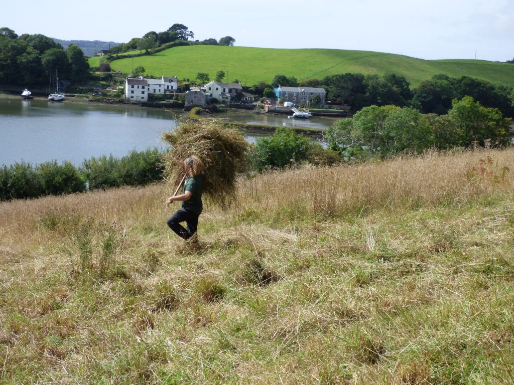One of the keen volunteers with a forkful of hay